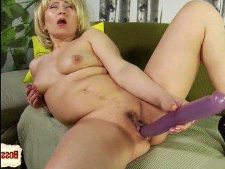 Голая, зрелая блондинка с волосатой мандой мастурбирует двойным фалоимитатором