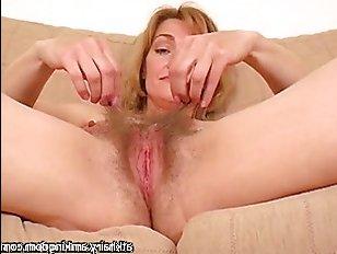 Зрелая мастурбирует волосатую пизду, получая оргазм