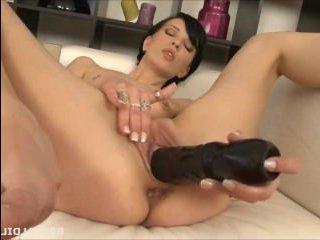 Молодая голая женщина мастурбирует двумя большими фаллоиметаторами